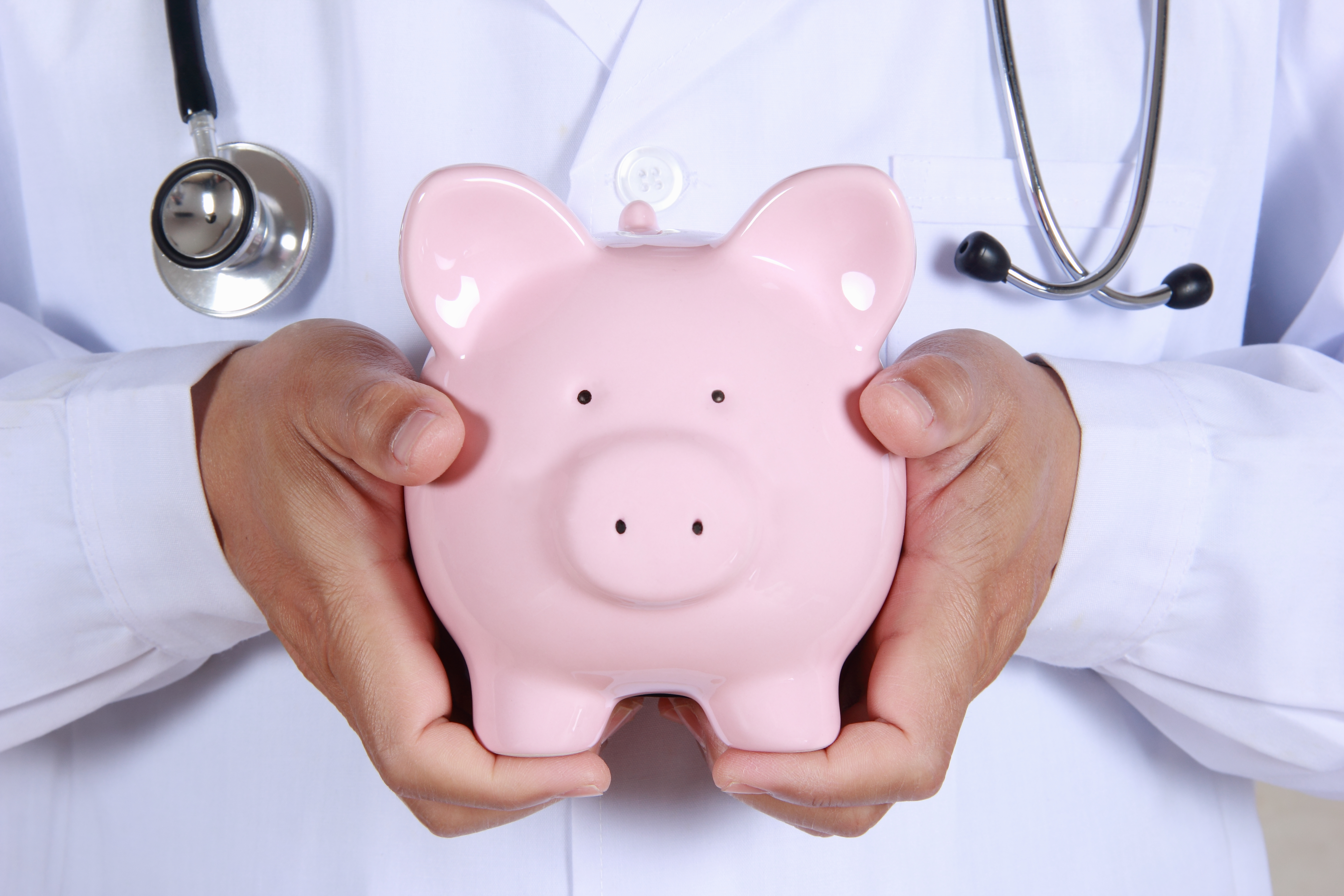 A person wearing a stethoscope holds a pink piggy bank.